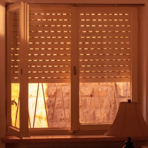 Window with roll-up shutter with variable slots which, when open, let in light.