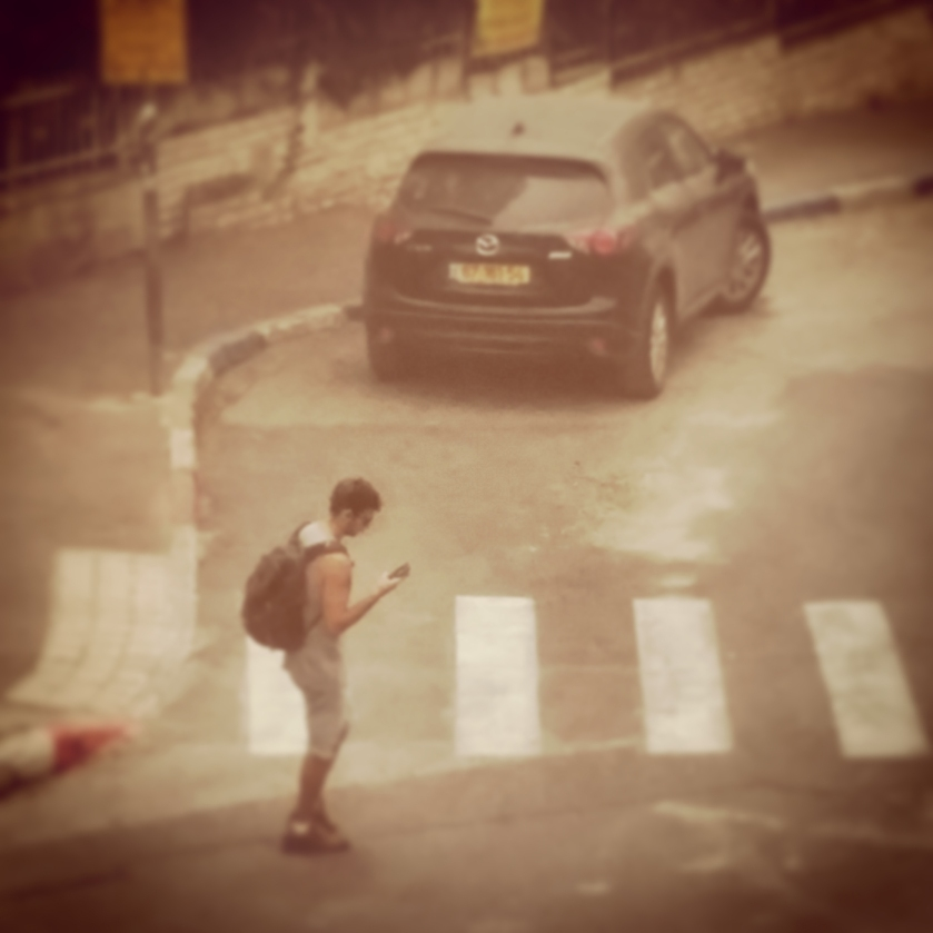Young Israeli crosses street in Jerusalem during the nations worst dust storm in history.